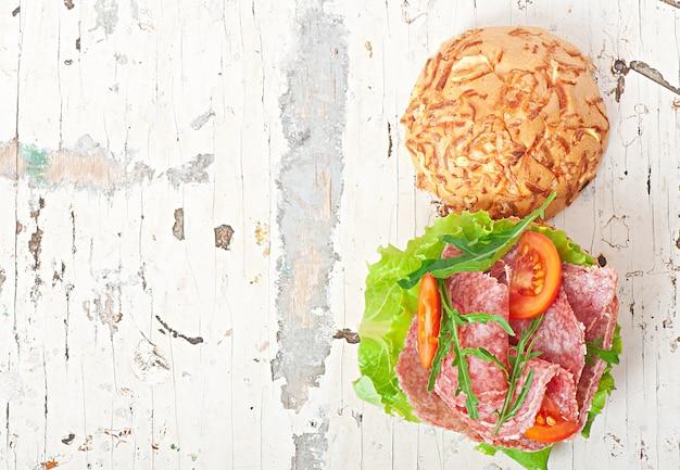 Sandwich met salami, sla, tomaat en rucola