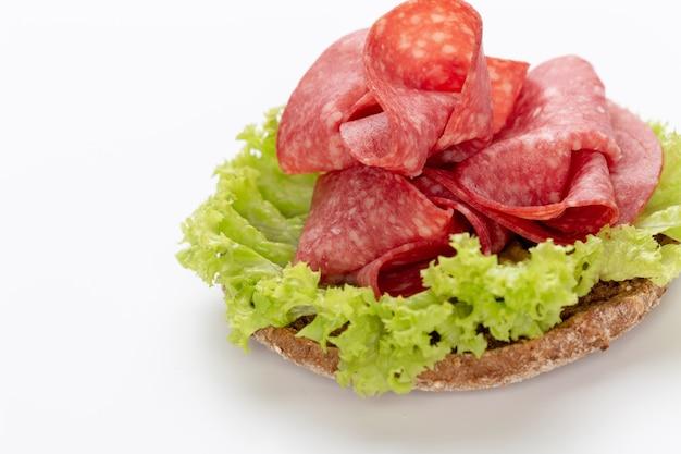 Sandwich met salami worst op witte achtergrond.