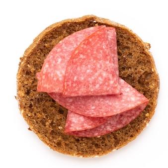 Sandwich met salamiworst op witte ondergrond.