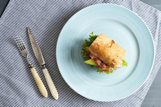 Sandwich met spek en avocado doorboord met een spies