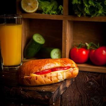 Sandwich met tomaat en kaas met sinaasappelsap en komkommers en sla in houten plank
