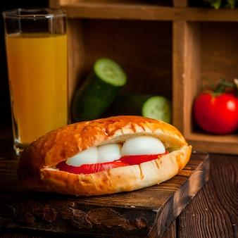 Sandwich met tomaat en kaas met sinaasappelsap en komkommers in houten plank