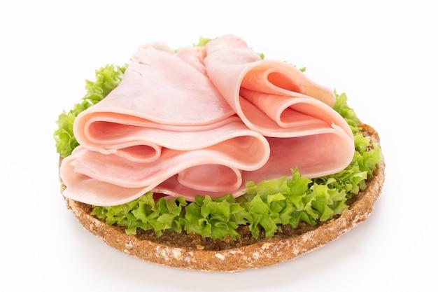 Sandwich met varkensvleesham op witte ondergrond.