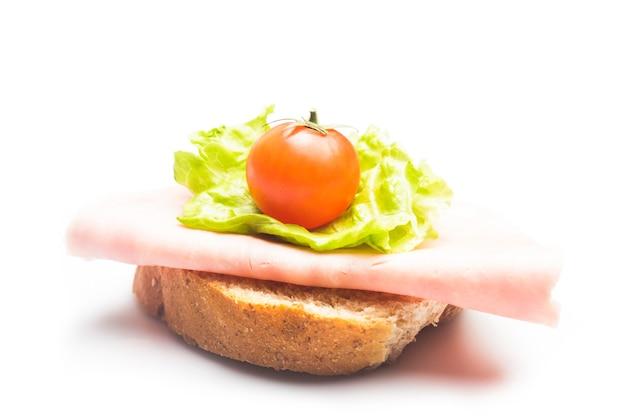 Sandwich met verse hamplak, rooster en kersentomaat op wit