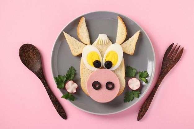 Sandwich met worst en ei in de vorm van een grappige stier