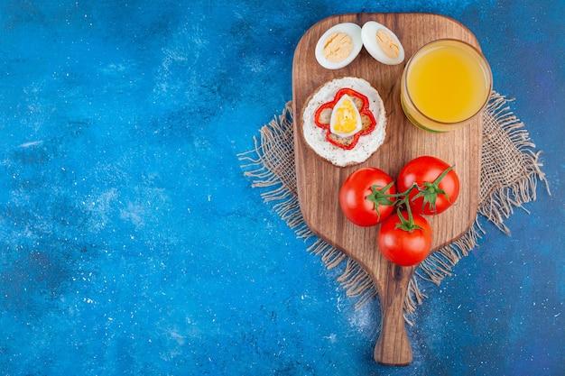 Sandwich met worst en hele tomaten op een snijplank op stukjes stof, op de blauwe achtergrond.