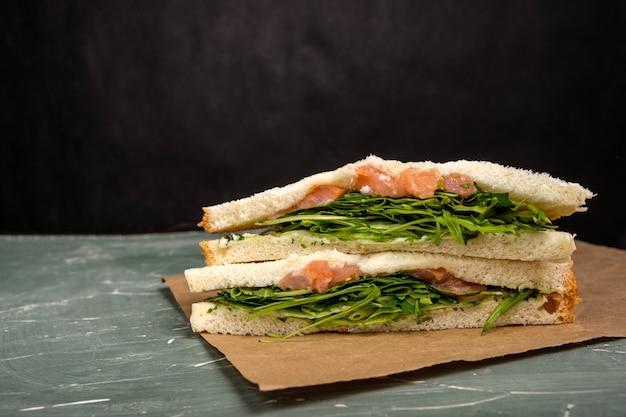 Sandwich met zalm, rucola en kaas op een groene achtergrond