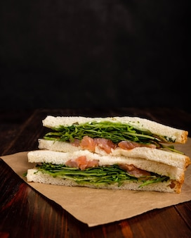 Sandwich met zalm, rucola en kaas op houten achtergrond