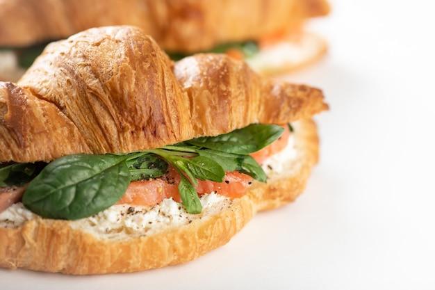 Sandwich met zalm, spinazie en roomkaas op een witte achtergrond, selectieve aandacht, close-up
