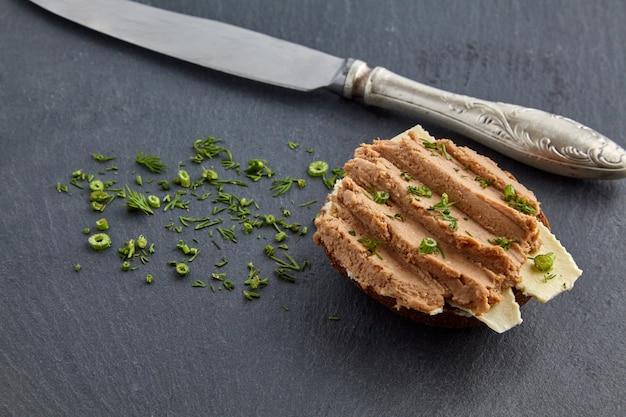 Sandwich met zelfgemaakte paté uitgespreid over brood en boter, gegarneerd met dille op een zwarte lei-plank