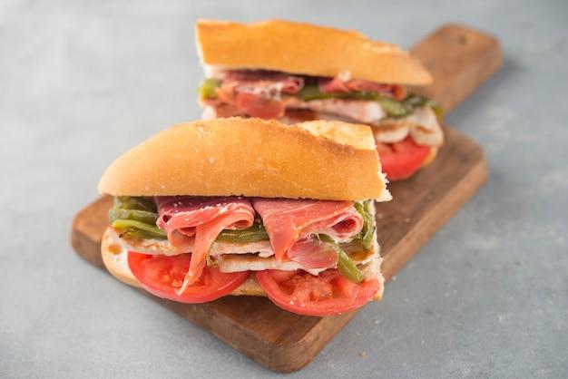 Sandwich serranito typisch in andalusië met ham, gren peper en gegrilde varkenslende