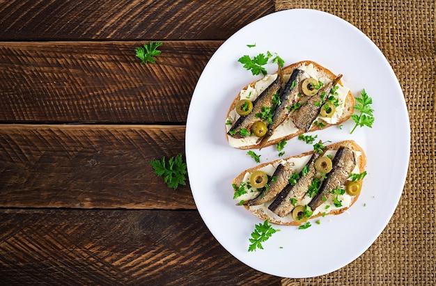 Sandwich - smorrebrod met sprot, groene olijven en boter op houten tafel. deense keuken. bovenaanzicht, boven het hoofd, plat gelegd