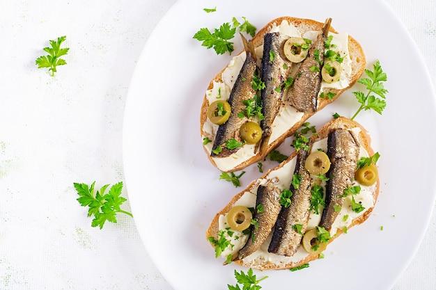 Sandwich - smorrebrod met sprot, groene olijven en boter op lichte tafel. deense keuken. bovenaanzicht, boven het hoofd, plat gelegd