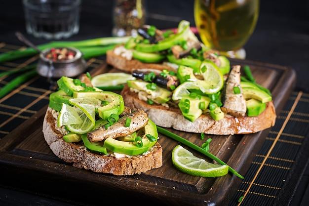 Sandwich - smorrebrod met sprotten, avocado en roomkaas op een houten bord.