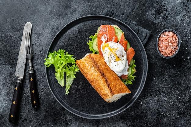 Sandwich toast met benedictus ei, gerookte zalm en avocado op brood. zwarte tafel. bovenaanzicht.