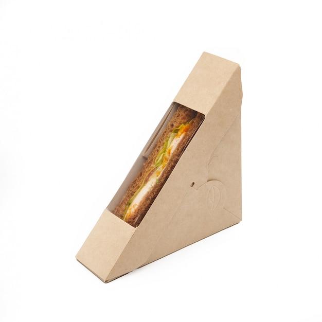 Sandwich toast met kip en kaas in een papieren ambachtelijke afhaaldoos geïsoleerd op een witte achtergrond, levering, eco-vriendelijk, wegwerp, recyclebaar fastfood-concept
