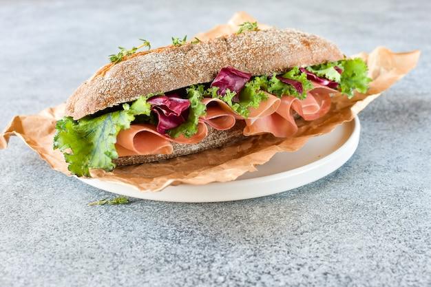 Sandwich van een prosciutto van het graangewassenbaguette, sla, boerenkool op een grijze achtergrond