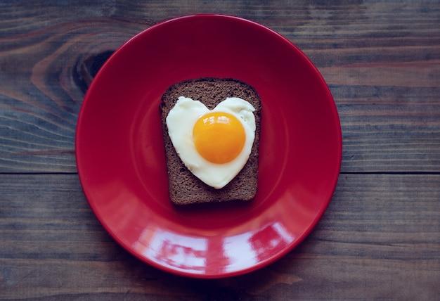 Sandwich van roggebrood met roerei in de vorm van een hart