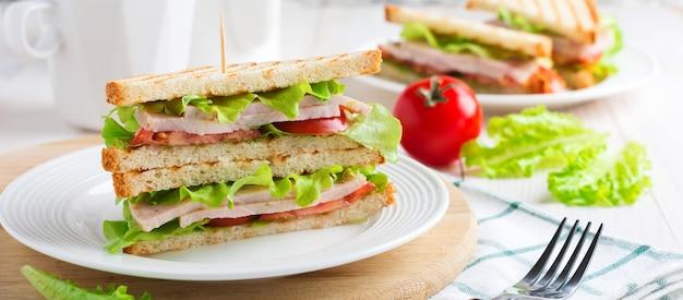 Sandwich voor het ontbijt met gevulde tomaten met ham en sla op een lichte houten achtergrond. selectieve aandacht.