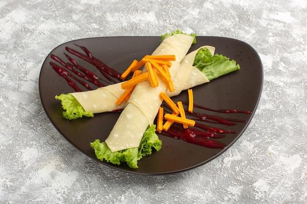 Sandwichbroodjes met groenten en groene salade samen met beschuit in donkere plaat
