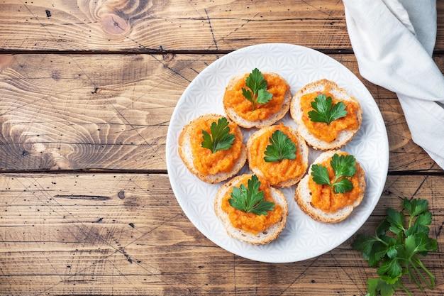 Sandwiches met brood courgette kaviaar tomaten uien. zelfgemaakte vegetarische gerechten. ingeblikte gestoofde groente. houten achtergrond bovenaanzicht, kopieer ruimte
