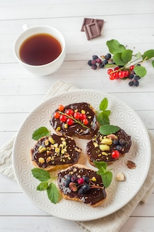 Sandwiches met chocoladepasta, pistachenoten en verse bessen op een bord.