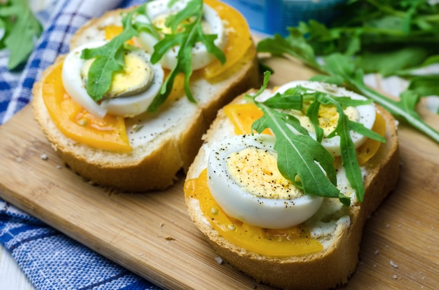 Sandwiches met gekookte eieren, gele tomaten en rucola.