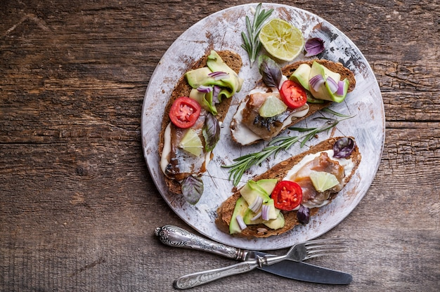 Sandwiches met gerookte makreel, avocado en rode ui.