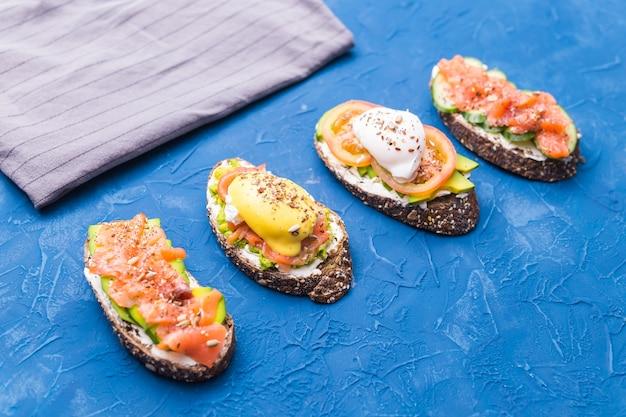 Sandwiches met gerookte zalm, eieren, saus en avocado op blauwe achtergrond. concept van ontbijt en