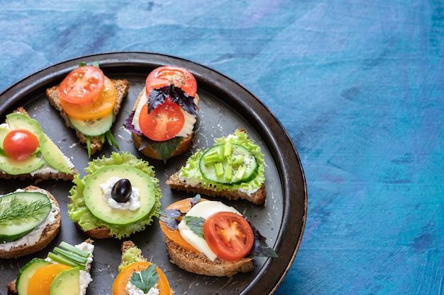 Sandwiches met groenten, kaas en kruiden op een metalen dienblad