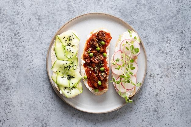 Sandwiches met groenten, radijs, tomaten, komkommers en microgreens op grijs. bovenaanzicht