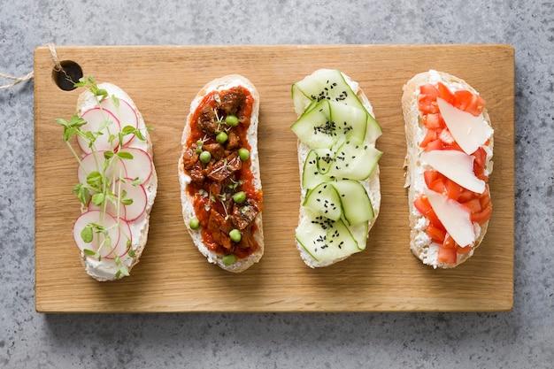 Sandwiches met groenten, radijs, tomaten, komkommers en microgreens op grijs. uitzicht van boven.