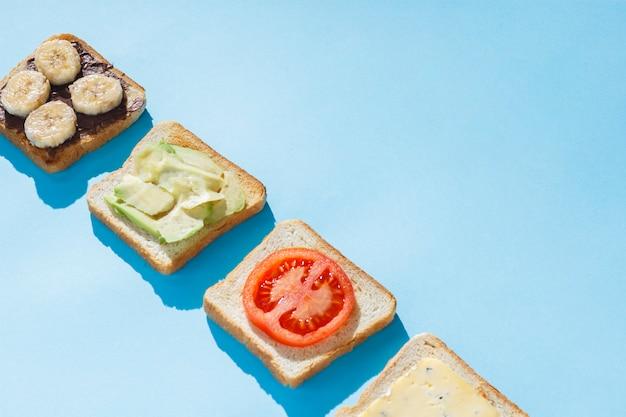 Sandwiches met kaas, tomaat, banaan en avocado op een blauwe ondergrond. plat lag, bovenaanzicht.