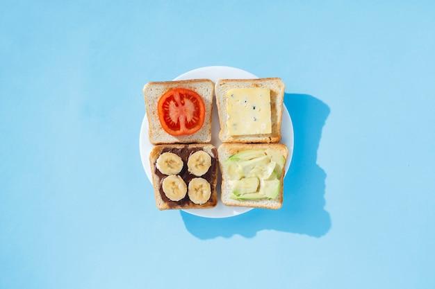 Sandwiches met kaas, tomaat, banaan en avocado op een witte plaat, blauwe ondergrond. plat lag, bovenaanzicht.