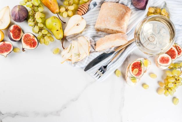Sandwiches met ricotta of roomkaas, ciabatta, verse vijgen, peren, druiven, walnoten en honing op tafel van wit marmer, met bovenaanzicht van wijnglas copyspace