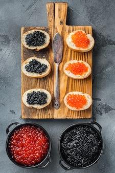 Sandwiches met rode en zwarte kaviaar stokbrood, op grijs
