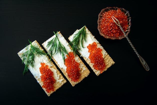 Sandwiches met rode kaviaar die op zwarte achtergrond wordt geïsoleerd