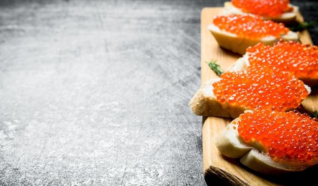 Sandwiches met rode kaviaar op een houten standaard. op zwarte rustieke tafel