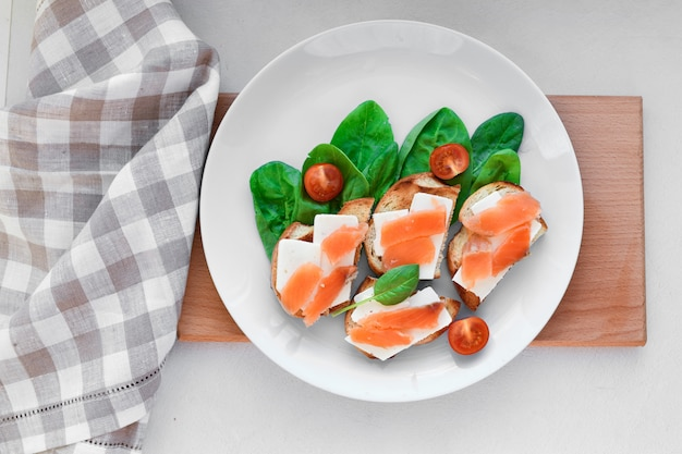 Sandwiches met rode vis op een witte plaat. versierd met groen