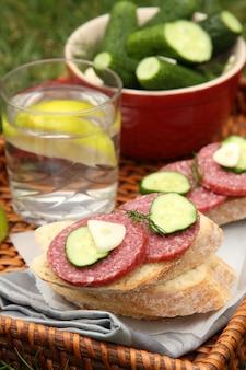 Sandwiches met rookworst en zelfgemaakte verse gezouten komkommers in de kom