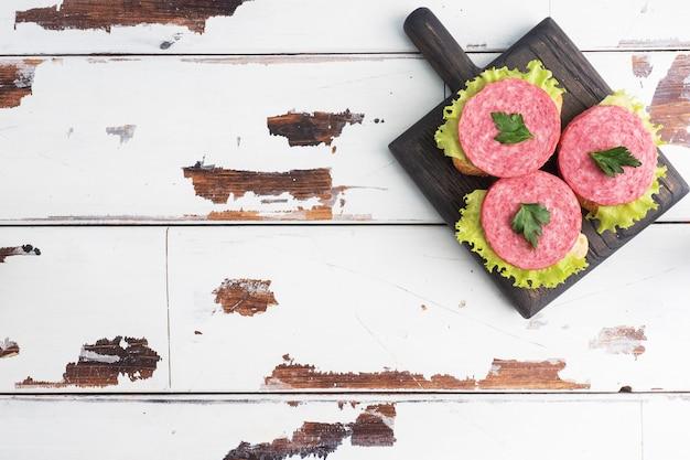 Sandwiches met slabladeren en gesneden salamiworst op een houten plank. kopieer ruimte bovenaanzicht