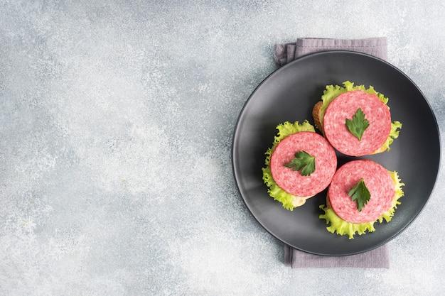 Sandwiches met slabladeren en gesneden salamiworst op zwarte plaat. kopieer ruimte bovenaanzicht