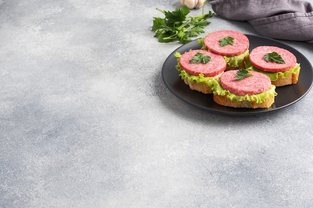 Sandwiches met slabladeren en gesneden salamiworst op zwarte plaat. ruimte kopiëren