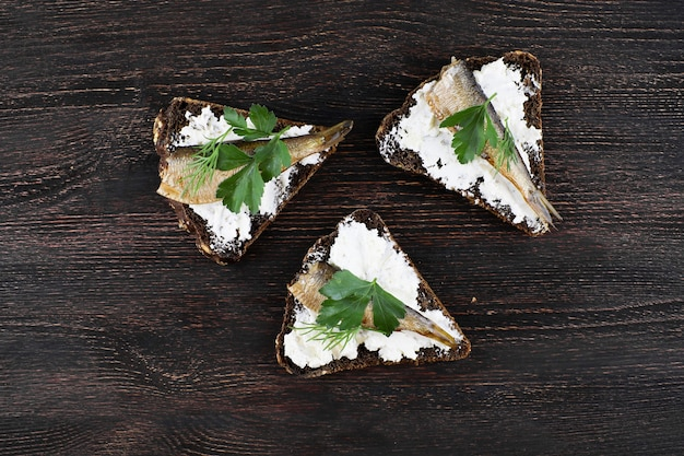 Sandwiches met sprot en kaassaus op houten bord