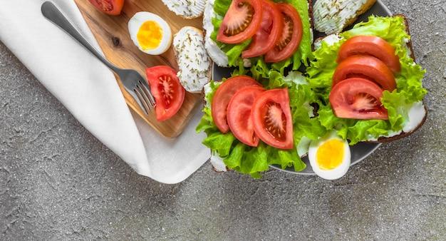 Sandwiches met tomaten, roomkaas, sla en gekookte eieren voor een gezonde lunch