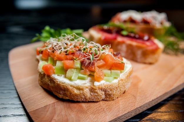 Sandwiches met vlees en groenten op houten tafel.