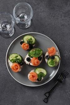 Sandwiches met zalm, komkommer, roomkaas en zwarte olijven op grijze achtergrond. zelfgemaakte vakantiesnack. uitzicht van boven
