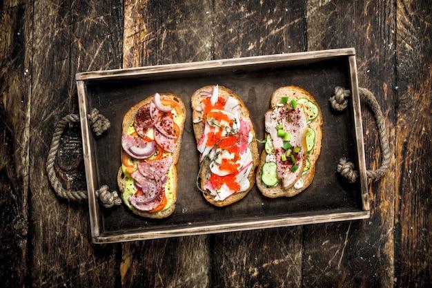 Sandwiches met zeevruchten, salami, baconnd verse groenten op houten tafel.