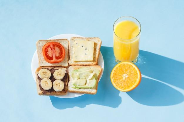 Sandwiches op een witte plaat, een glas met jus d'orange, een blauw oppervlak. plat lag, bovenaanzicht.