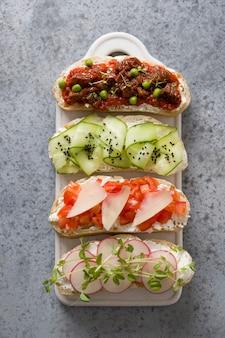 Sandwiches op toast met groenten, radijs, tomaten, komkommers en microgreens op grijs. uitzicht van boven.